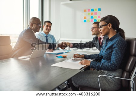 Two young multiracial business teams reaching an agreement in negotiations stretch across the table in the conference room to shake hands - stock photo