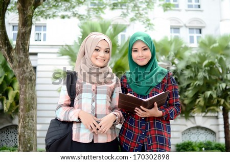 Two young muslim girl reading book - stock photo