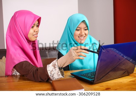 two young muslim women doing a group discussion by using a laptop