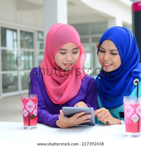 Two young Muslim women with beauty smile using mobile tablet