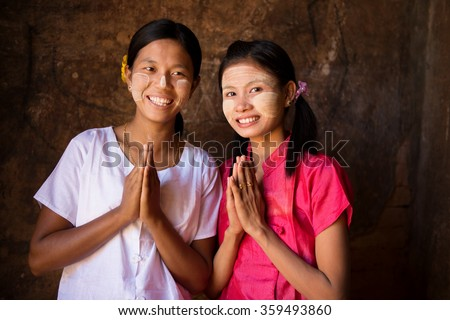 Two young Myanmar women in a traditional welcoming gesture.