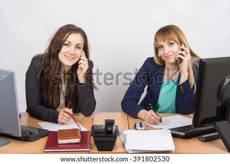 Two young office employee talking on mobile phones at his desk - stock photo
