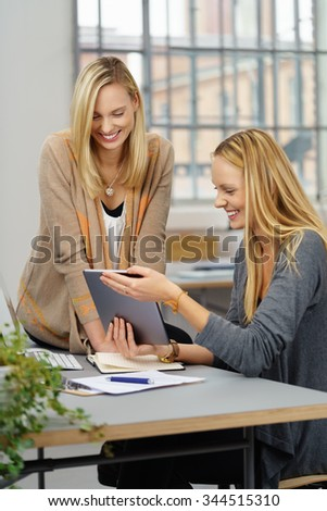 Two Young Office Women Watching Funny Video on Tablet Computer with Happy Facial Expressions.