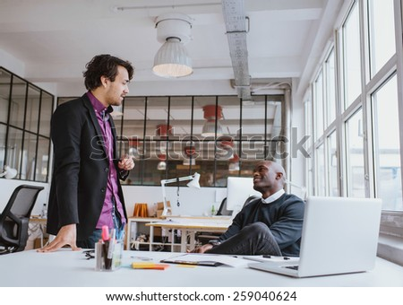 Two young office workers having a casual meeting at desk. Mixed race business people discussing work in office. - stock photo