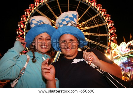 Two young Oktoberfest guests enjoying life with lights in the background - stock photo