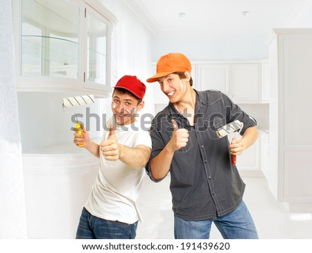 Two young painters with paint rollers