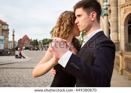 two young people - a man in black suit and a woman wearing black dress - dancing tango outside; a musician is playing romantic songs - stock photo