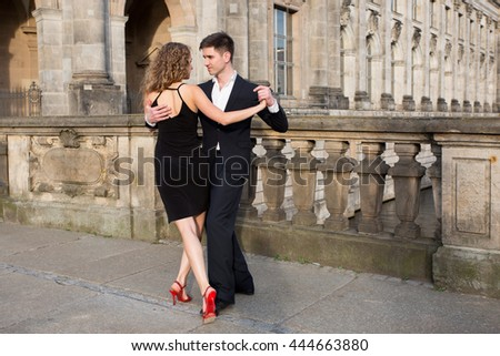 two young people - a man in black suit and a woman wearing black dress - dancing tango outside on the old stone bridge - stock photo