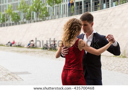 two young people - a man in black suit and a woman wearing red dress - dancing tango outside - stock photo