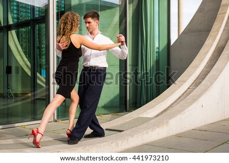 two young people - a man in white shirt and a woman wearing black dress - dancing tango outside somewhere in the city near modern buildings - stock photo
