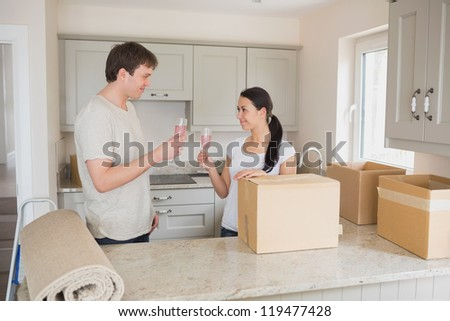 Two young people celebrating move into new home with champagne in kitchen - stock photo