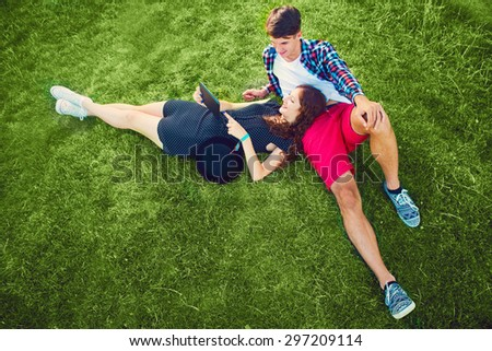 Two young people enjoying on the grass with tablet - stock photo