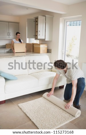 Two young people furnishing the kitchen and living room for a relocation - stock photo