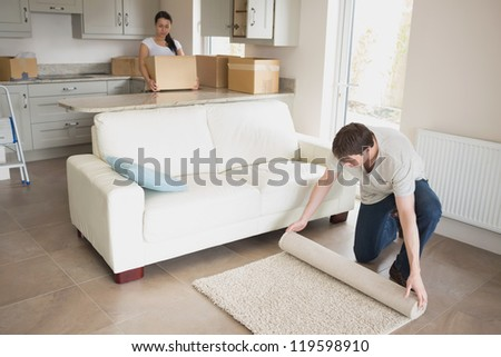 Two young people furnishing the kitchen and living room while relocating - stock photo
