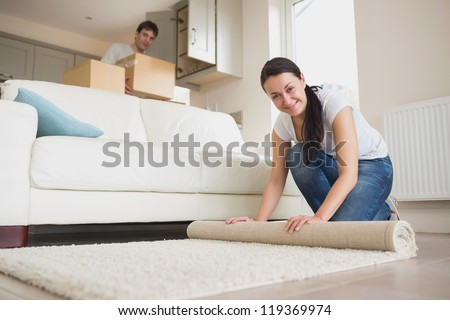 Two young people furnishing the living room of new home - stock photo