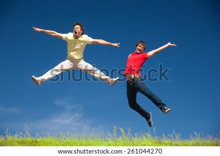 Two young people jump on top of hill in park - stock photo