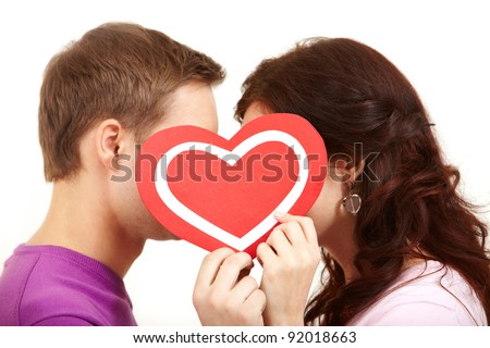 Two young people kissing behind a paper heart