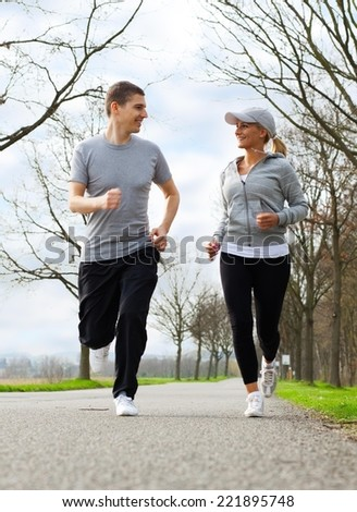 Two young people running in nature. - stock photo
