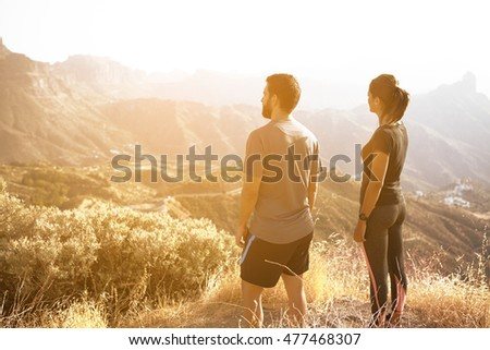 Two young people standing and admiring the view on a mountain in full sunlight with their hands to their sides