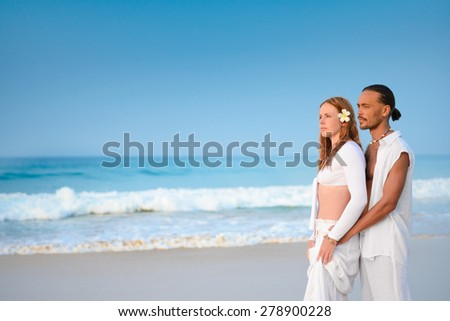 Two young people standing on sea shore at dusk