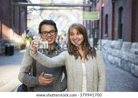 Two young people taking a selfie with smartphone on city street