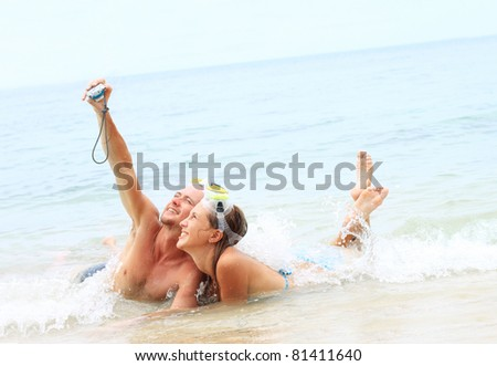 Two young people with the masks making photo of themselves in the sea - stock photo