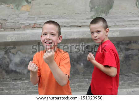 Two young playful Caucasian boy boxing at street - stock photo