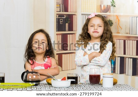Two young preschooler girls looking upset refusing to eat their meal - stock photo