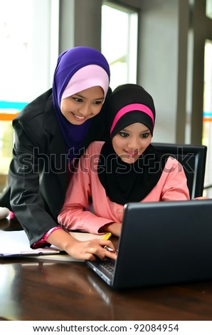 Two young pretty Asian muslim business woman in head scarf  happy with looking at laptop