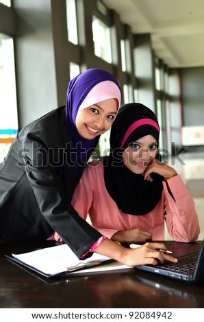 Two young pretty Asian muslim business woman in head scarf  smile