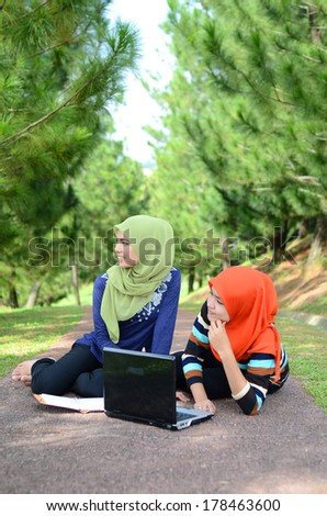 Two young pretty Asian muslim college girl with book and laptop