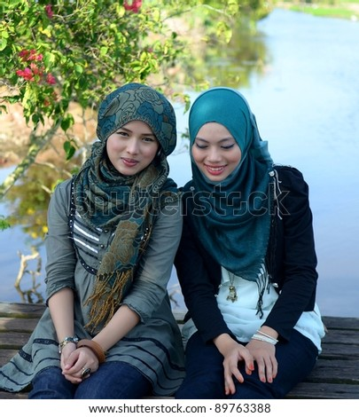 Two young pretty Asian muslim college relaxing - stock photo