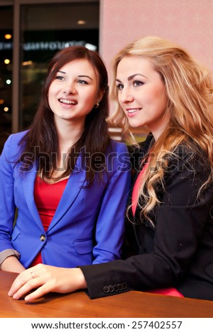 Two young pretty caucasian girls with long hair chatting and having fun at a cafe