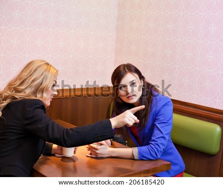Two young pretty caucasian girls with long hair chatting and having fun at a cafe. One points to something interesting - stock photo
