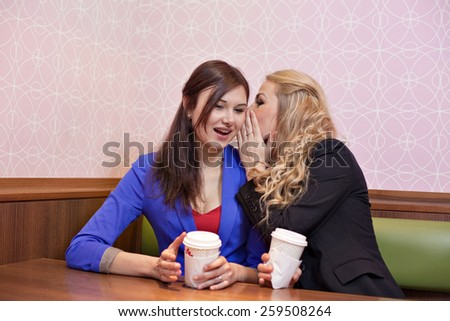 Two young pretty caucasian girls with long hair drinking coffee, whispering and having fun at a cafe - stock photo
