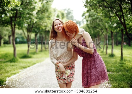 Two Young Pretty Girls Having Fun Outdoors in Summer Time. Freedom Youth Concept. Happy Women Laughing. Selective Focus on Red Hair Woman. - stock photo