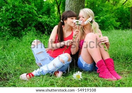 two young pretty girls with flowers sitting on a grass - stock photo