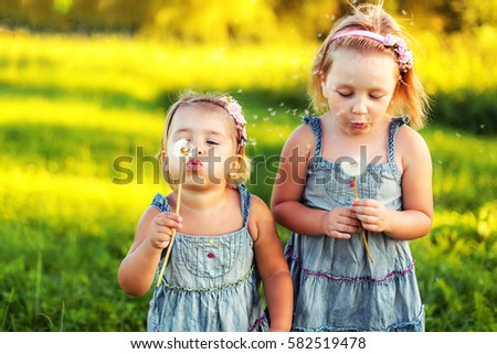 Two young pretty sister-girls are  pretty girls and having fun in a bright warm summer rays of sunshine in a similar dresses and blowing dandelion