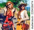 Two young pretty surprised girls, say you hello. Two best friends having fun together at park walk with retro bikes, wearing vintage clothes hats and sunglasses. Outdoor fashion portrait. - stock photo