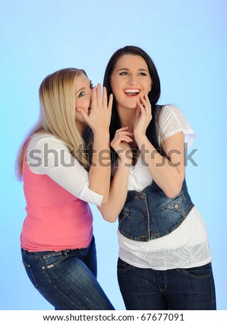 Two young pretty woman gossiping and enjoying conversation. isolated on blue background - stock photo