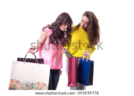 two young pretty woman standing isolated on white background paper shopping bags from the store. girlfriend shows off a new purchase - stock photo