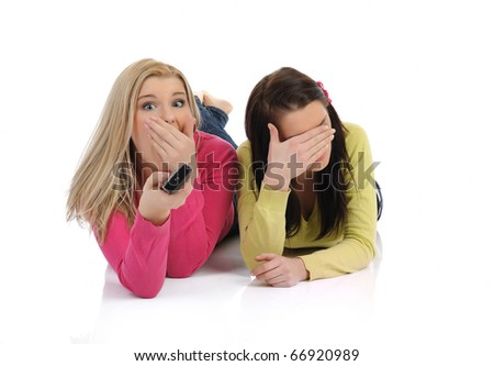 two young pretty woman watching television and switching channels on remote control - stock photo