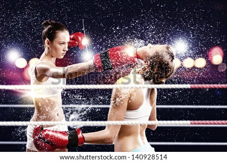 Two young pretty women boxing in ring - stock photo