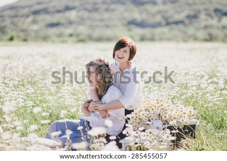 Two young pretty women having picnic with tea in chamomile field. Female friendship