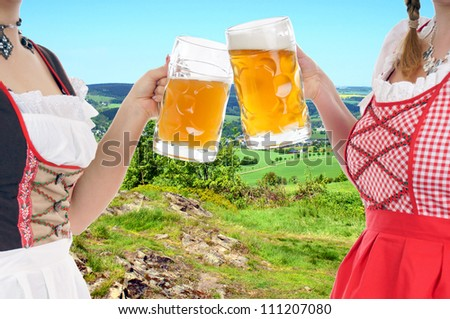 Two young pretty women in dirndl with beer mug in nature / munich beer festival - stock photo