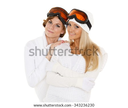 Two young pretty women in winter clothes and ski glasses are standing on a white background. Winter sports. - stock photo