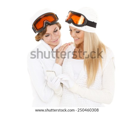 Two young pretty women in winter clothes and ski glasses  with a mobile phone on a white background. Winter rest. - stock photo