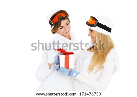 Two young pretty women in winter clothes and ski glasses with gift box on a white background. Winter sports. - stock photo