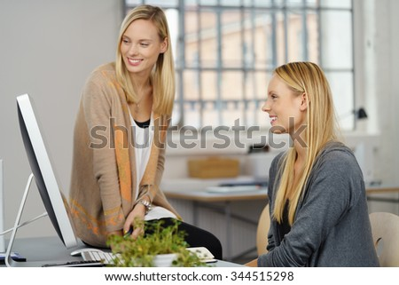 Two Young Professional Office Women Looking at Computer Together with Happy Facial Expressions.