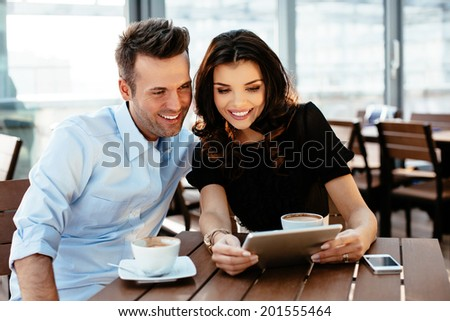 Two young professionals browsing internet during a coffee break - stock photo